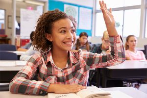 Schoolgirl at desk in elementary school raising her hand